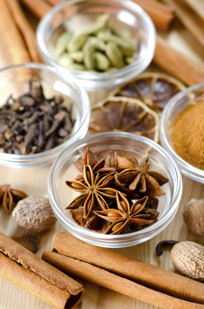 Aromatic spices like cloves, cinnamon sticks, and whole nutmeg on a wooden table.