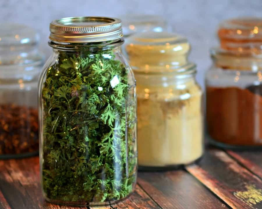 Mason jar filled with dehydrated parsley, and spice jars in the background