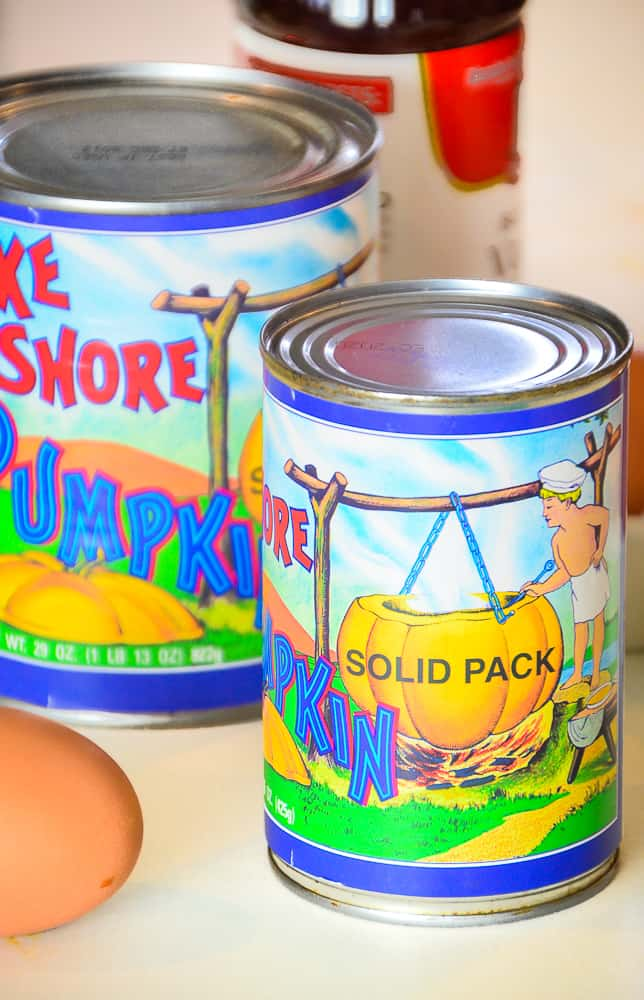 A 15-ounce can on Lake Shore Solid Pack Pumpkin sitting on a kitchen counter with an egg in the background.