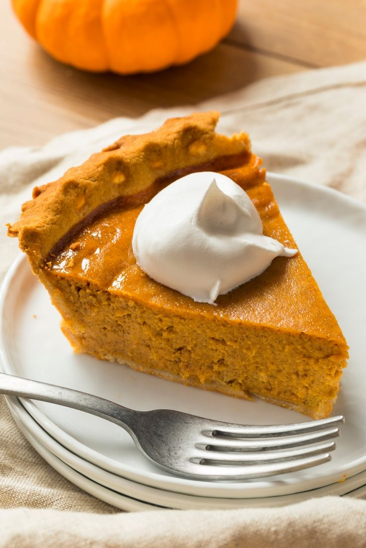A slice of pumpkin pie sitting on a stack of 3 white plates with a fork. There's a linen napkin on the wooden table and a small pumpkin in the background.