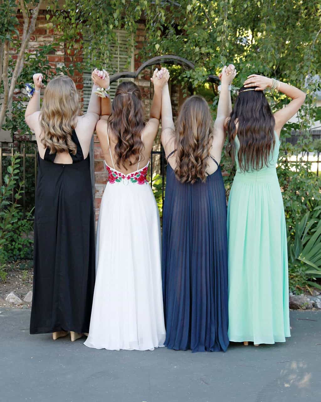 4 girls in prom gowns facing away from camera holding hands