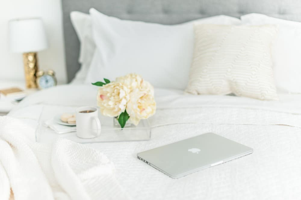 Macbook on bed with a tray holding cookies and coffee. Alarm clock and lamp on bedside table.