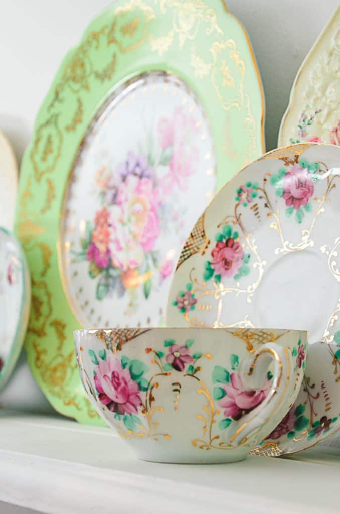A vintage teacup and saucer with a floral rose pattern on a white shelf.