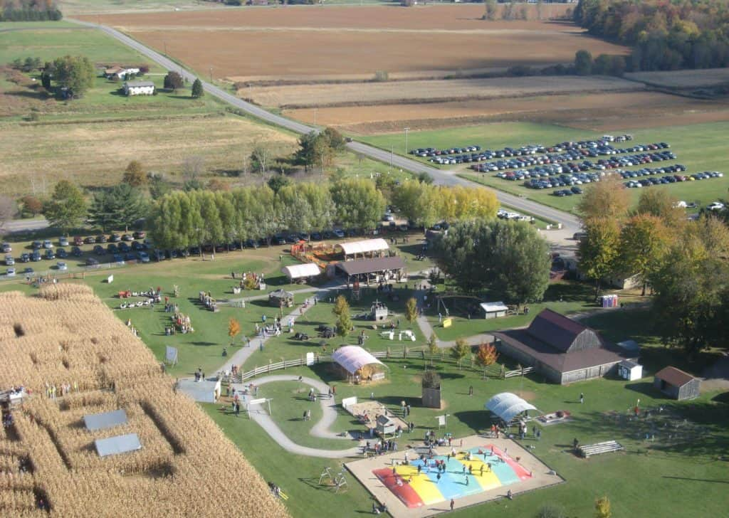 Birdseye view of the fall activities at Long Acre Farms, showing the corn mazem giant bounce pillow, farm animals and wagon rides, along with the farm market and pumpkin patch