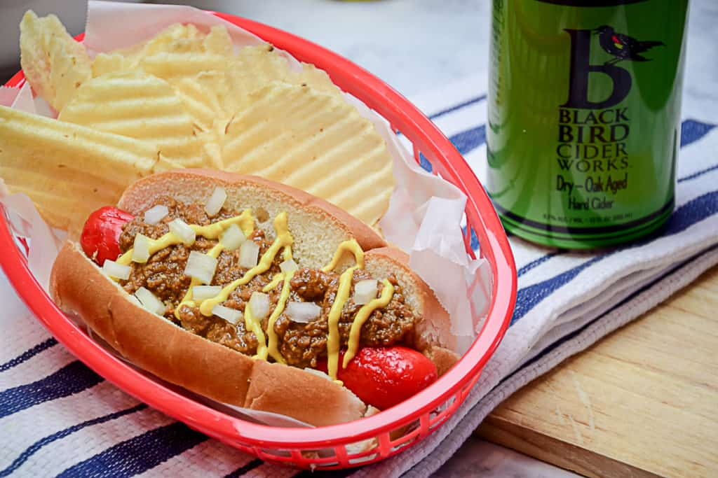 A red plastic food basket holding a Michigan style hot dog with mustard and chopped onions on a new england style bun, sitting next to a can of Upstate New York hard cider.