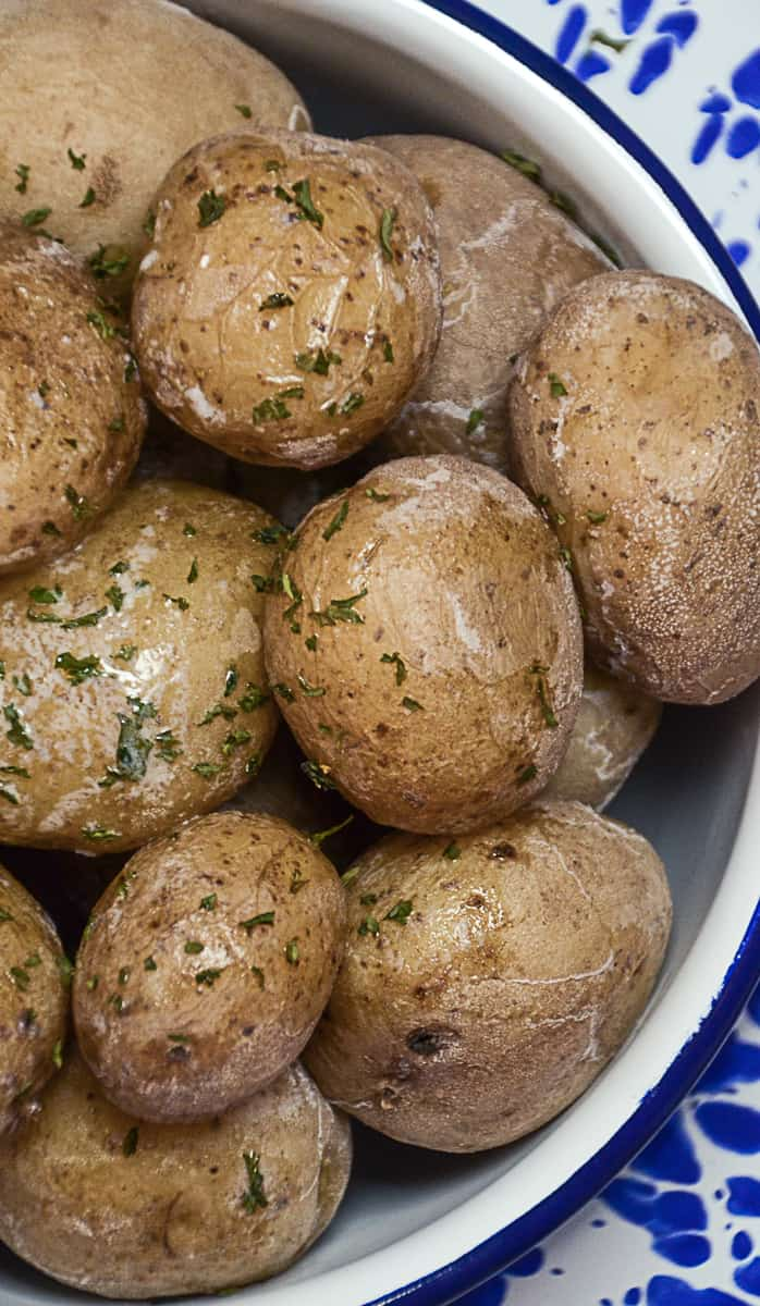 Overhead picture of salt potatoes in  a white bowl.