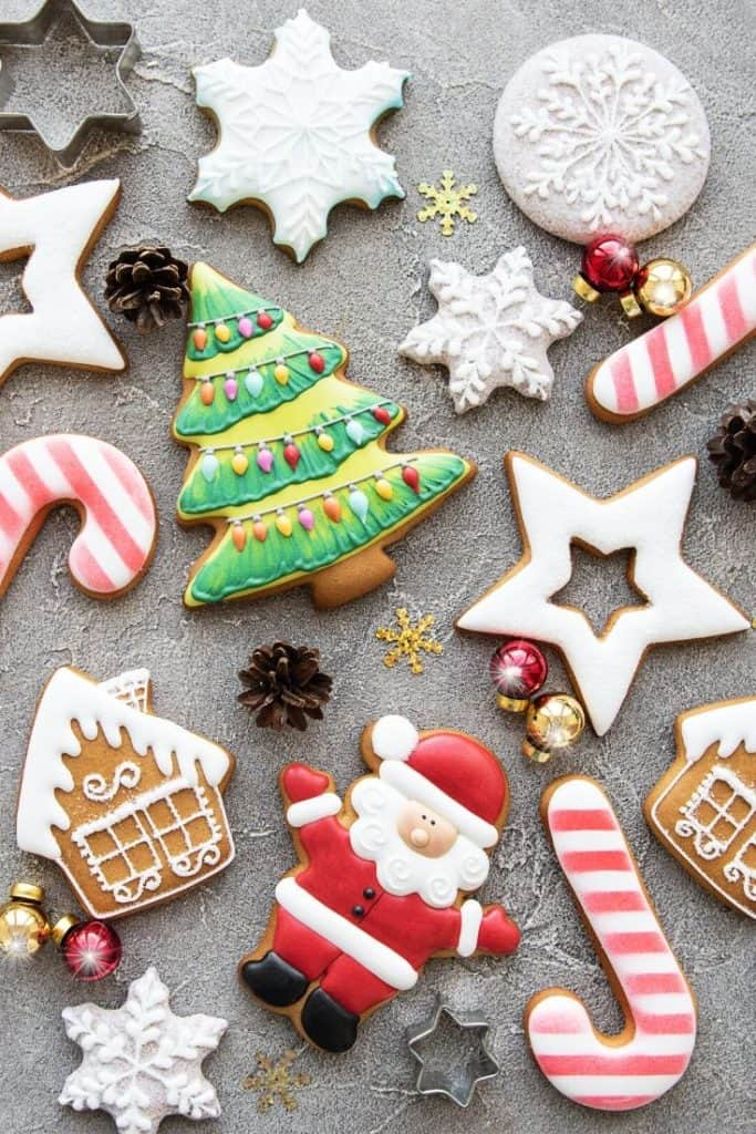 Cut out sugar cookies on a grey background with mini ornaments and cookie cutters.
