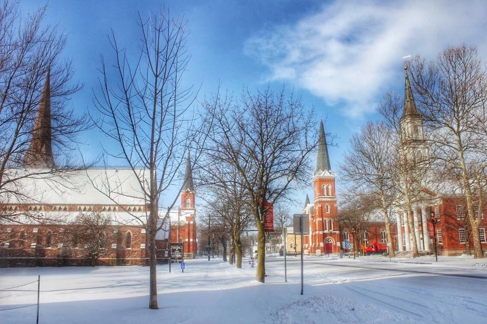 The four churches of Palmyra NY with Snow covered streets and sidewalks and a bright blue skiy.