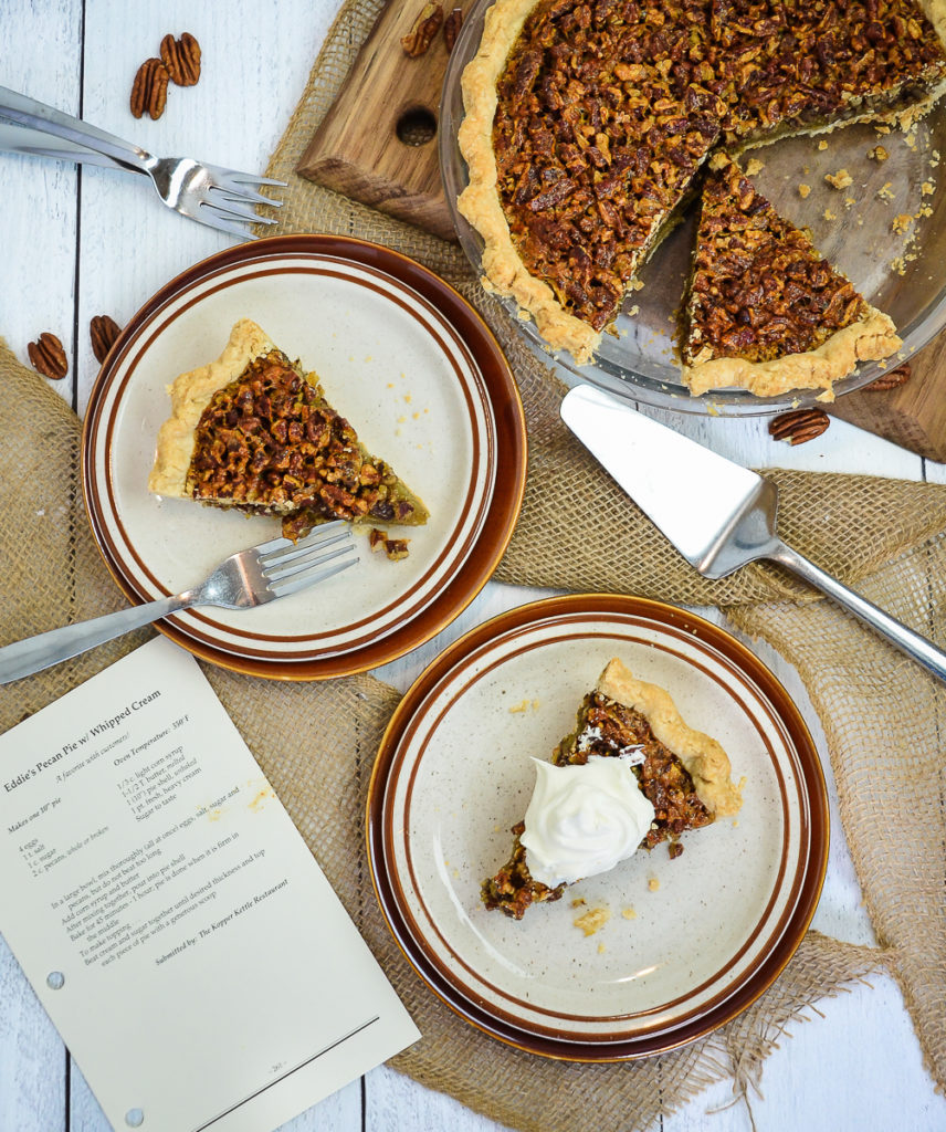A tabletop overhead view of two brown and white plates that each have 1 slice of pecan pie, with the remainder of the pie in the pie dish sitting to the side. 1 of the slices of pecan pie is topped with fresh whipped cream.