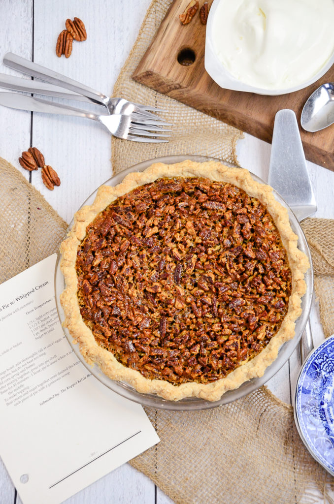 Overhead view of homemade pecan pie on a white table. The recipe for the Kopper Kettle pecan pie is sitting beside the pie.