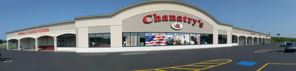 """Panoramic view of the outside of Chanatry's Hometown Market in Utica New York. The beige store features a large red sign reading """"Chanatry's"""""""