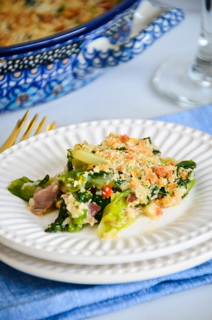 Utica greens on a small white plate, on a blue tablecloth with a wne class andblue casserole pan slightly out of focus in the background