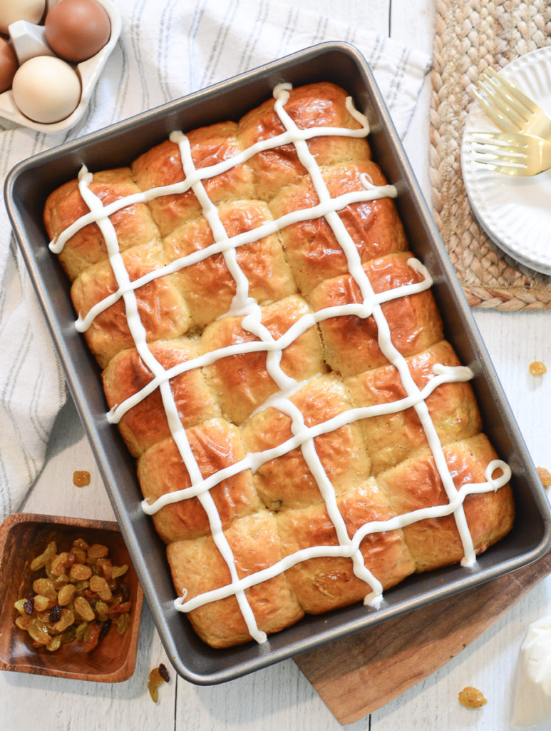A 9x13 baking pan filled with golden brown hot cross buns on a white wood table. The pan is sorrounded by a grey and white kitchen towel, a  and small bowl of raisins, brown eggs in a egg holder.