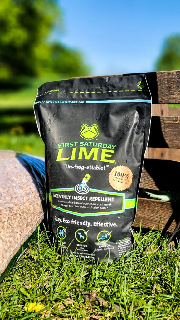5 lb bag of First Saturday Lime sitting on grass outdoors, a wooden crate and bag of pine bedding are in the background.