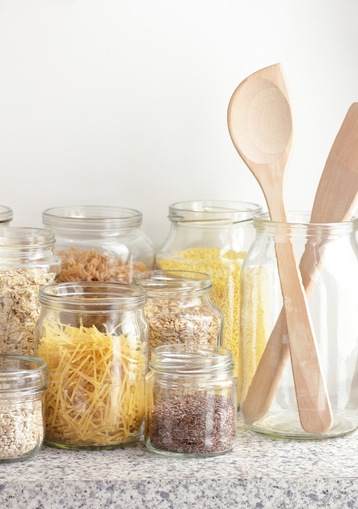 Glass jars containing dried pastas, beans and oats in front of a white background.