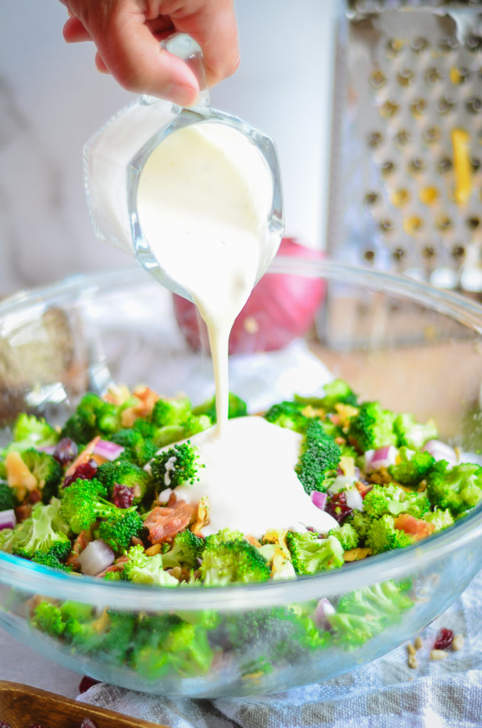 Broccoli salad in a large clear glass bowl. A creamy maoy-based dressing is being poured onto the salad from a small glass pitcher.