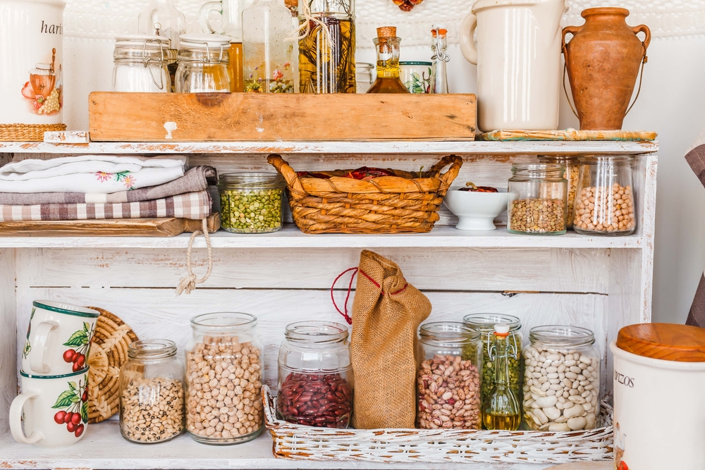 White wooden pantry shelves holding glass jars with dried beans, vintage kitchen linens, wicker baskets and baking supplies.